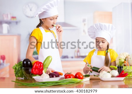 Two children in the kitchen with the food starting to cook