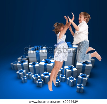 Two children jumping happily surrounded by gift boxes - stock photo