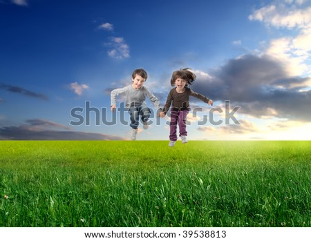 two children jumping in a grass field - stock photo