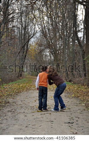 two children kiss while on a walk in autumn - stock photo