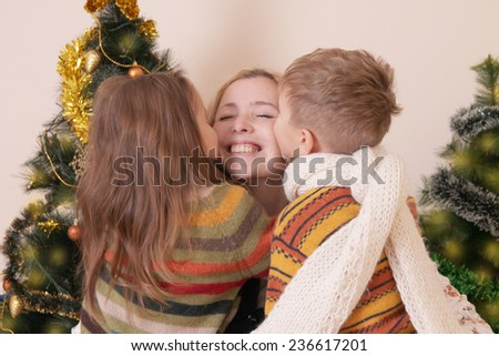 Two children kissing their mother under Christmas tree - stock photo