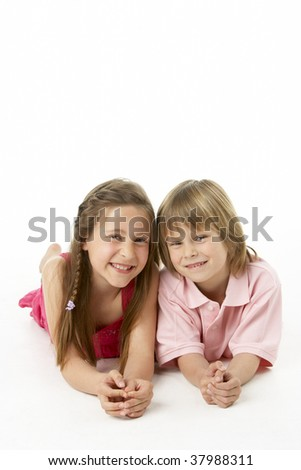 Two Children Laying on Stomach in Studio - stock photo