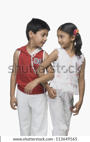 Two children looking at each other with their arm in arm - stock photo