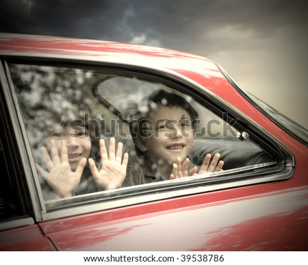two children looking trough car window - stock photo