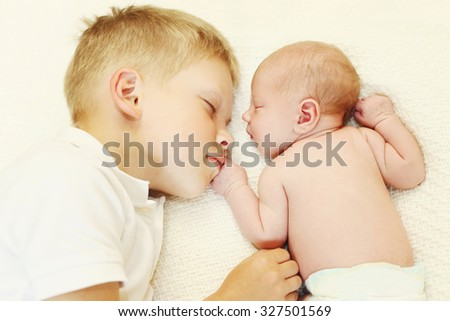 Two children lying on bed, eldest brother hugging youngest baby, top view