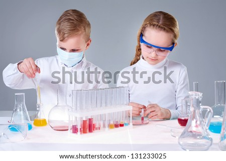 Two children making chemical experimentsin laboratory - stock photo