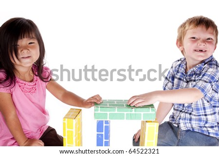 Two children of different races are playing with blocks. - stock photo