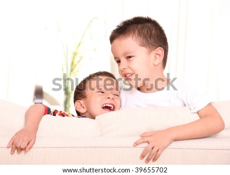 Two children on a sofa, smiling and playing