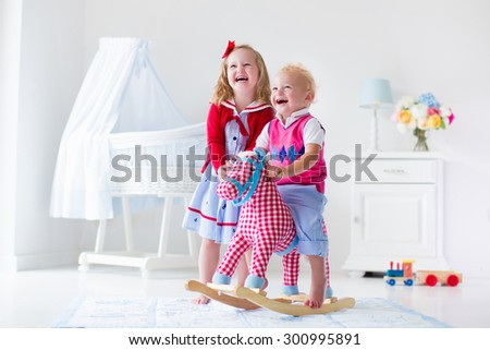 Two children play indoors. Kids riding toy rocking horse. Boy and girl playing at day care or kindergarten. Beautiful nursery for baby and toddler. Toys for preschool child. Brother and sister at home - stock photo