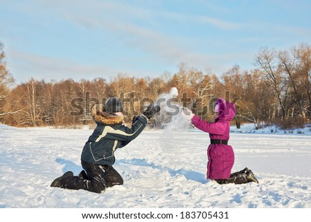 Two children play with snow on bright winter day - stock photo