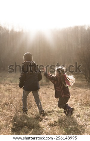 Two children playing on a meadow in very early spring - stock photo
