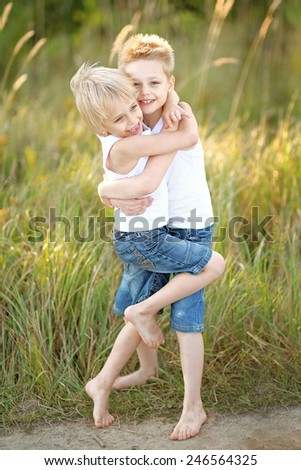 two children playing on meadow in summer - stock photo