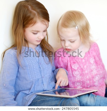 Two children playing with a digital tablet at home