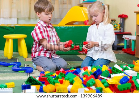 Two children playing with blocks on the floor at home - stock photo