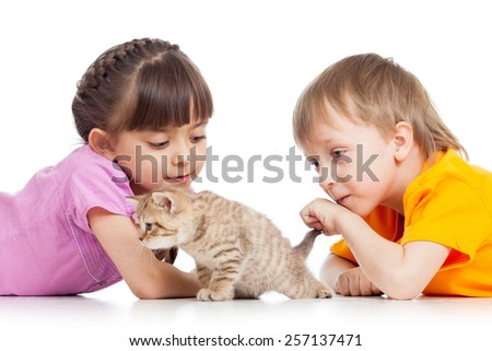two children playing with cute funny kitten - stock photo