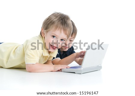 Two children playing with the laptop lying on the floor - stock photo