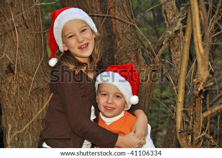 two children pose by a tree wearing santa hats - stock photo