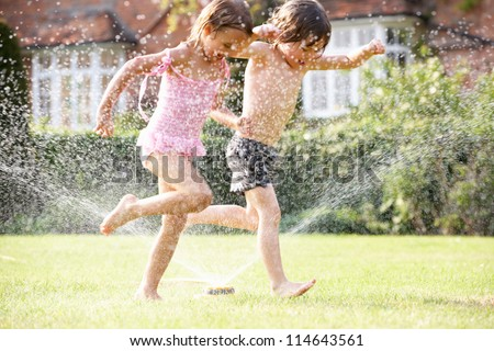 Two Children Running Through Garden Sprinkler - stock photo