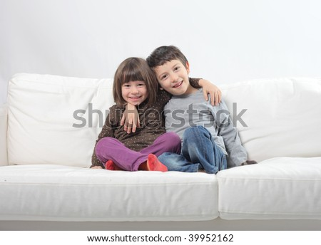 two children seated on sofa - stock photo