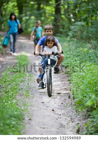 Two children share a bicycle as they travel on forest. Family on background - stock photo