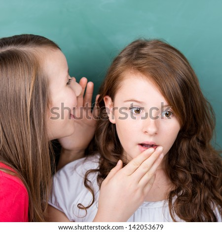 Two children sharing a secret in front of blackboard - stock photo