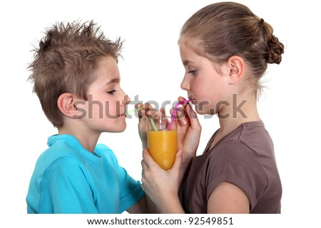 Two children sharing orange juice - stock photo