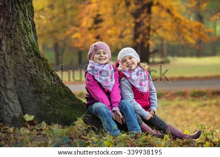 Two children sitting in a park on a tree trunk - stock photo