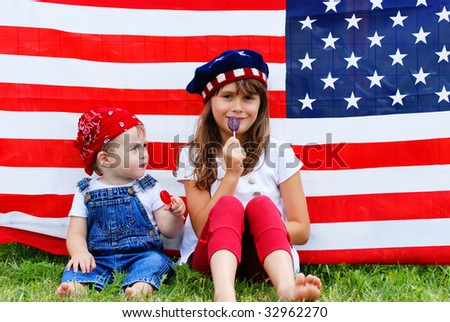 Two children sitting next to an american flag eating suckers