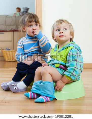 Two children  sitting on chamber pots in home interior - stock photo