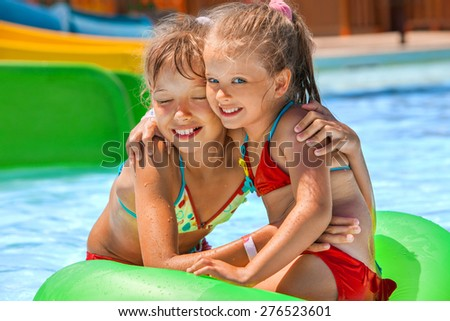 Two children sitting on green inflatable ring in swimming pool. - stock photo