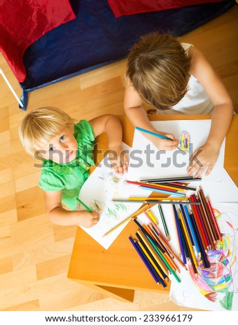 Two children sketching with paper and pencils in home interior