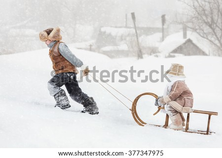 Two children sledding with mountain warm winter day - stock photo