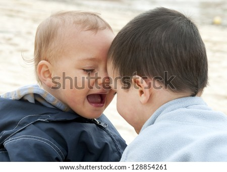 Two children,  small brother boys playing together outdoors. - stock photo