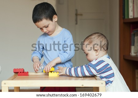 Two children, small toddler or a baby child and his older brother, playing together at home with building blocks on a low table. - stock photo