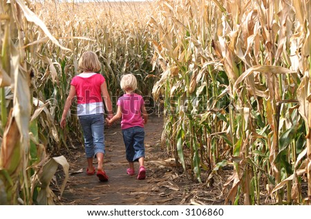 Two children spending an autumn walk together.  (Entering a corn maze). - stock photo