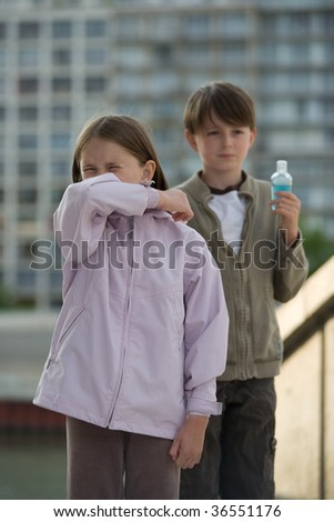 Two children stand in an urban setting, one sneezing into their elbow, the other holding a bottle of hand cleanser. - stock photo