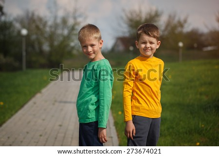 Two children standing back to back. Two cheerful boys of the friend. Outside
