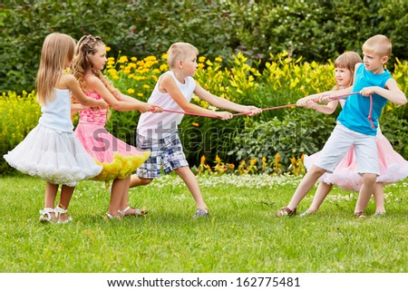 Two children teams play tug-of-war - stock photo