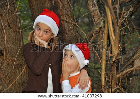 two children think they hear santa in the woods - stock photo