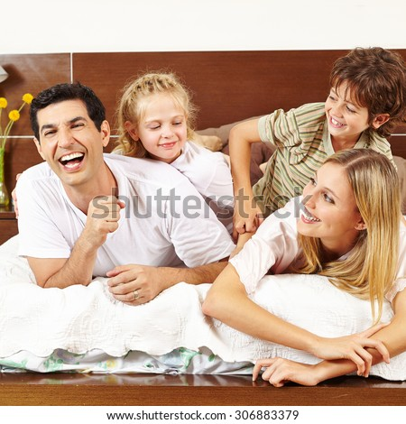 Two children tickling their parents in bed in the morning - stock photo