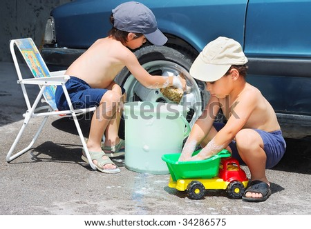 Two children washing car and toy car