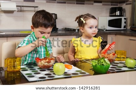Two children who eat healthy food in the kitchen - stock photo