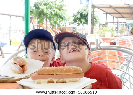 Two children with hotdogs at a restaurant - stock photo