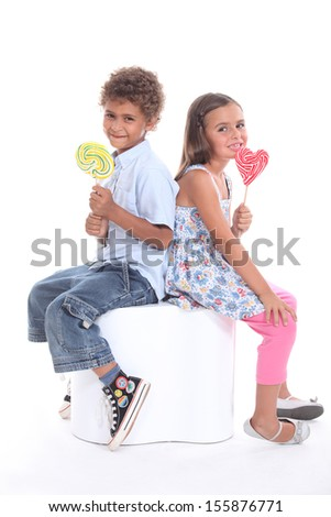 Two children with lollipops - stock photo