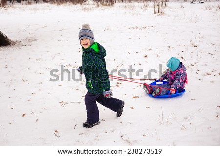 Two children with sled in a forest  - stock photo