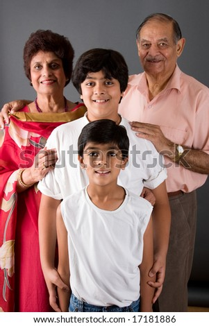 Two children with their grandparents against a gray background