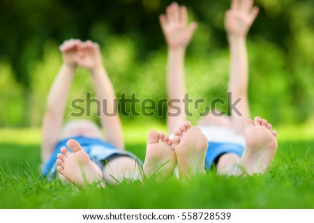 Two childrens feet on grass outdoors in summer park