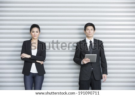 Two Chinese business colleagues using modern portable tech device's  - stock photo