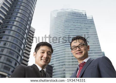 Two Chinese business men in modern Asian city. Asian businessman smiling & looking at the camera with skyscraper office buildings above. - stock photo