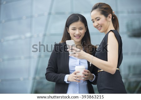 Two Chinese business women with Smart Phone in a modern urban setting. - stock photo